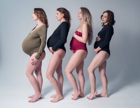 Four beautiful pregnant woman in swimsuit standing one behind the other on a white background.