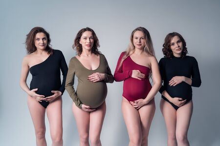 Four beautiful pregnant woman in swimsuit standing on a white background.