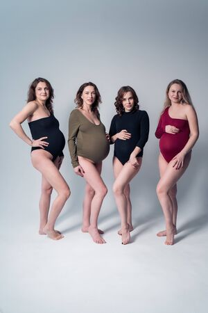 Pregnant girls. Girls in bikinis on a white background.