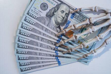 Pirate money. Skeleton hand holding dollars.