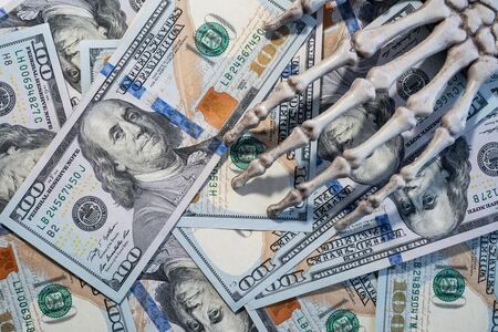 Skeleton hand lying on the dollars.