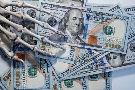Skeleton hand holding banknotes of dollars. 版權商用圖片