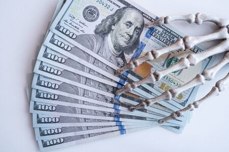 Dollars bills in skeleton hands isolated on white table, money
