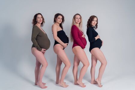 Four beautiful pregnant girls in bikinis stand each other on a white background. 版權商用圖片