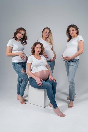 Four beautiful pregnant girls in the Studio. 版權商用圖片