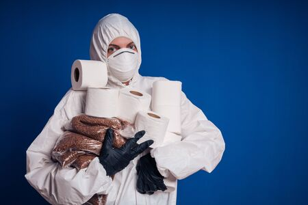 Girl in a protective white suit holds rolls of toilet paper and buckwheat in her hands. Coronovirus panic. 版權商用圖片