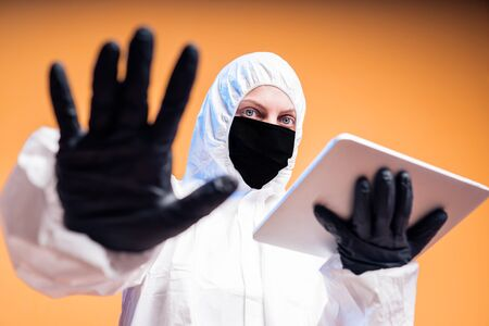 Scientist in protective suit, a white mask and black gloves holding a tablet in his hand. 版權商用圖片