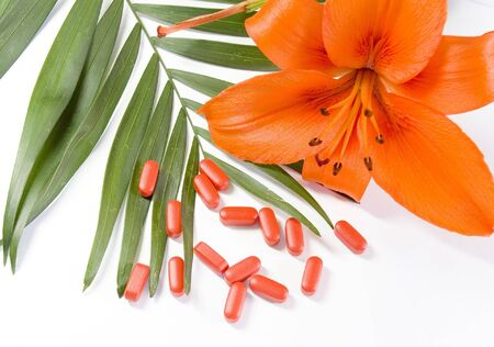 pills, flower and the green leaf on a white background