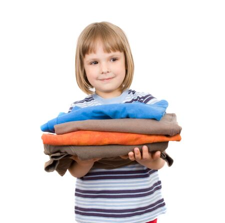 little girl with a pile of T-shirts Stock Photo
