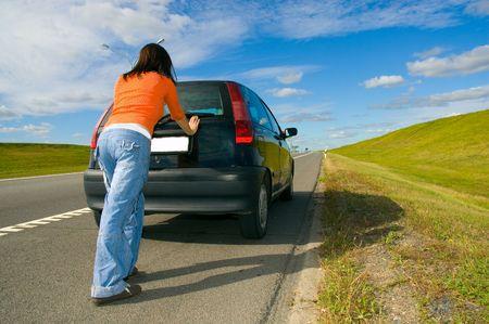 startpunt: vrouw duwen van een auto Stockfoto