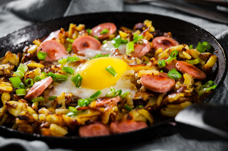 fried egg with sausage and potato in a frying pan on wooden table