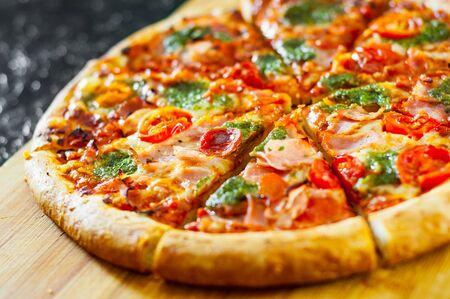 sliced Pizza with Mozzarella cheese, Ham, Tomatoes, pepper, Spices and Fresh Basil pesto sauce. Italian pizza. Reklamní fotografie