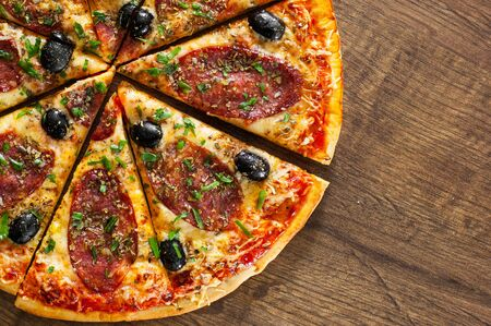 slices of Pizza with Mozzarella cheese, salami, pepper, pepperoni, olives, Spices and Fresh Basil. Italian pizza on wooden background