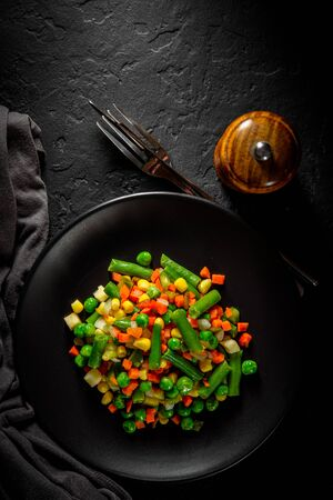 Mixed vegetables on a black plate on Dark grey black slate background