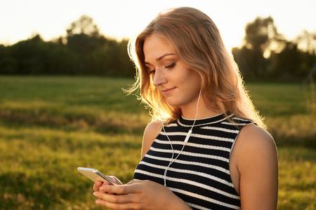 Portrait d'une mignonne femme aux cheveux clairs qui lit quelque chose sur son téléphone intelligent et écoute la musique avec ses écouteurs sur le fond vert. Beautiful youg girl portant un T-shirt à rayures et tenant son téléphone mobile Banque d'images - 67313491