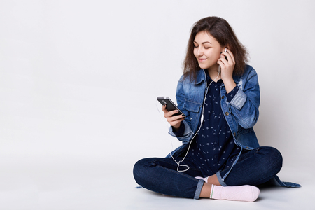 Photo of happy smiling beautiful girl messaging via social networks and using earphones for listening to music looking relaxed and cheerful on white floor. Fashion lifestyle concept. Stock Photo