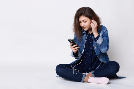 People, technology and communication. A pretty young dark-haired girl listening to the music with her cell-phone holding her hand on her earphones sitting crossed legs in white studio