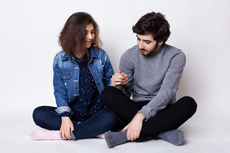 two people with others: A happy couple sitting on the floor crossed legs holding each other`s hands being happy and pleased to be together. Young bearded man touching his girlfriend`s hand with love. Two young people in love Stock Photo