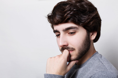A concentrated young hipster with thick dark eyebrows stylish haircut and beard having thoughtful expression remembering something from his past looking mysteriously down holding hand on chin