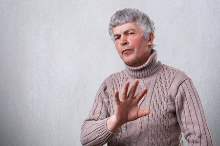 An angry frowning mature man having negative expression showing refusing sign with palm. Negative human emotion face expression feeling body language. Showing denial with no sign.