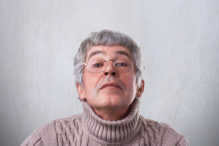 comically: A close-up of funny grandfather in glasses looking happily through eyeglasses having fun. An elderly man having mysterious expression looking comically into camera while posing in studio Stock Photo