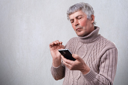 frowned: A serious mature man holding smartphone in his hand looking attentively into the screen.  Senior man reading text message on phone having frowned expression. People, technology, lifestyle.