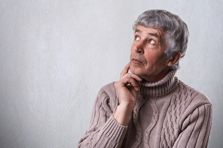 A close-up of dreamy elderly male holding his hand under chin looking aside having thoughtful faraway expression. Mature man daydreaming about something that makes him happy. Good memories Stock Photo