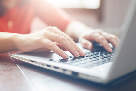 Female hands typing on keyboard of laptop surfing Internet and texting friends via social networks, sitting at wooden table indoors. Tecnology and communication concept/ Selective focus.
