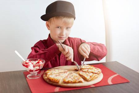 A little blond boy with blue eyes wearing red shirt and stylish cap sitting in cosy cafe eating delicious pizza and ice-cream looking sulky. A child having lunch at restaurant. Stock Photo