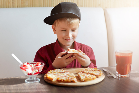 A little boy dressed in red shirt and modern cap siting in restaurant at table tasting delisious pizza and ice-cream drinking tomato juice. A child having lunch in cosy cafe.