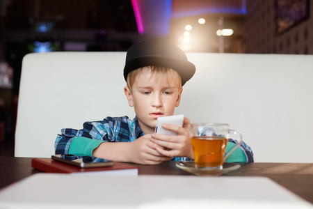 newsfeed: A little child dressed in stylish clothes siting in modern cafe interior, using cell phone, checking newsfeed on his social network accounts. Handsome little boy surfing internet on mobile