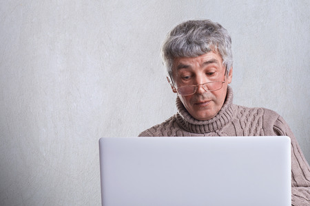 A surprised senior man dressed in sweater having gray hair and wrinkles using his laptop surfing in the internet. A lonely handsome grandfather reading news online being at home.