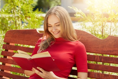 People, rest, hobby, vacation concept. Cheerful fair-haired woman in red sweater holding her favourite book reading funny stories. Pretty female reading book at wooden bench admiring weather Stock Photo
