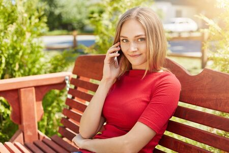 Blonde woman with freckles having gentle smile while sitting at wooden comfortable bench in park and communicating with her best friend over mobile phone telling her news. Positive woman outdoors Stock Photo