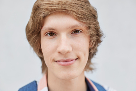 dimple: Close up portrait of handsome young boy with stylish hairdo, dark narrow eyes, thin lips, pure healthy skin and dimple on cheek looking direcrtly into camera having serious expression. People, beauty Stock Photo