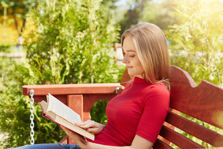 Summertime and leisure concept. Sideways portrait of attractive schoolgirl wearing red sweater reading attentively book preparing for lessons while sitting at wooden bench outdoors admiring nature