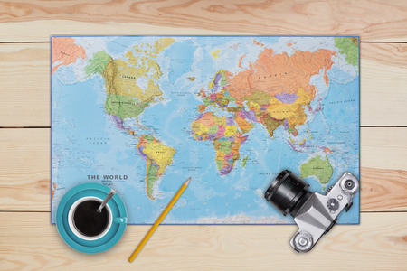 Map, old camera, cup of coffee and pencil laying on wooden desk. Necessary equipment of traveler or tourist. Top view of traveler baggage and retro camera with copy space. Travelling concept