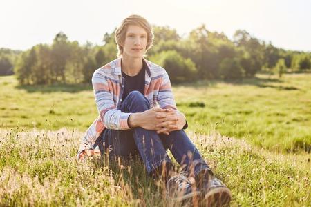 Hübscher Kerl mit dem tragenden Hemd und den Jeans der modischen Frisur, die auf grünem Gras der Wiese Sonnenlicht und Frischluft entspannend und bewundernd sitzen. Erfreuter Mann, der sich draußen während seiner Sommerferien entspannt Standard-Bild - 81858887