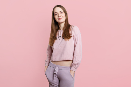 Slim sporty female model wears casual sport clothes, keeps hands in pockets, looks directly into camera, isolated over pink background. Fashionable young woman poses in studio, rests at home 免版税图像 - 108450607