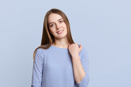 Portrait of pretty lovely young woman with dark ahir, pleasant charming smile and appearance, wears fashionable blouse, stands alone against blue background. Positive emotions and people concept