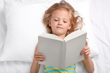 Pretty small preschooler reads attentively interesting story, holds opened book, lies in bed, enjoyes reading before sleep, has good rest. Clever little girl reads fairy tale. Hobby, children concept