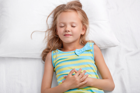 Charming lovely small child with messy hair, healthy skin, keeps hands together, lies on comfortable bed, has pleasant dreams during afternoon nap, Children, good night and sleeping concept.