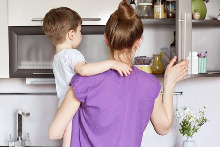 Domestic work, children and motherhood concept. Busy housewife tries to find necessary products in shelf of kitchen, holds small kid on hands as he is very naughty, does simultaneous work at time