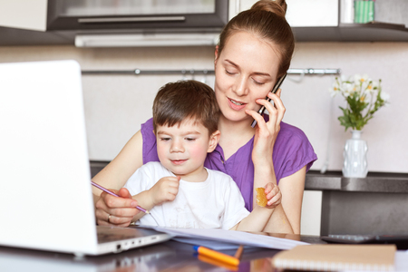 Portrait of young mother works freelance on laptop computer, communicates with someone via smart phone, looks after her little son who doesn`t go to kindergarten. Working mum with male child.