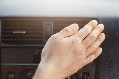 La mano del hombre en el calentador o acondicionador del automóvil regula la temperatura en el automóvil mientras conduce. Accesorios o panel del coche. Concepto de acondicionamiento.