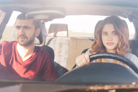 Couple in car on road trip: concentrated experienced female driver sits at wheel and her husband at front passanger seat, look in window with focused dreamy expressions. Transport, road and travel