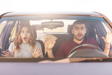 Frightened terrified couple in car can`t control speed, drive fast, afraid of being safe, scream with shock as have accident, being very emotional. People, safety, driving and crash concept. Imagens