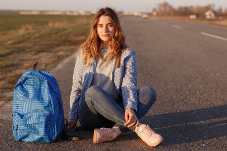 Serious female hitchhiker sits crossed legs on asphalt road with her bag, enjoys travelling in countryside, explores unknown places, likes freedom, looks pensively directly at camera, feels lonely