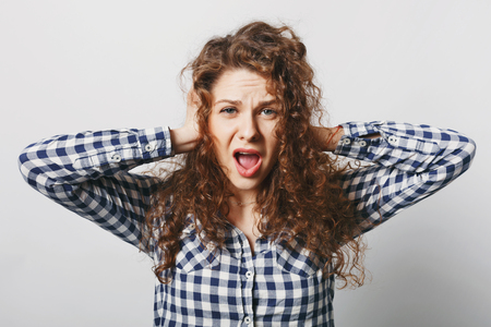 Negative emotions and people. Desperate female keeps hands on ears, ignores someone, opens mouth widely, screams with hopelesness, feels anxiety and frustration, isolated over white background Stock Photo