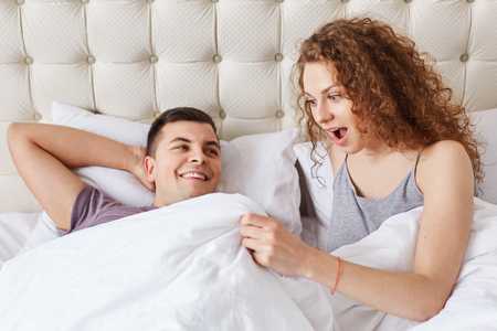 Shocked female looks under white blanket, being surprised with size of boyfriend`s genitails or sees man`s erection. Satisfied couple have good relationships. Intimate and lifestyle concept. Standard-Bild